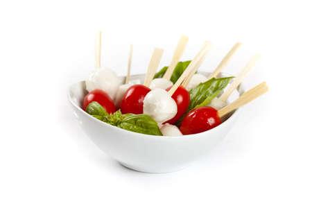 Caprese salad on a sticks with mozzarella, tomatoes and basil. Selective focus. photo