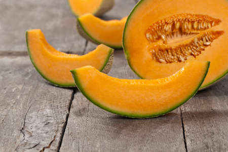 summer food: Fresh melons on old wooden background. Selective focus. Stock Photo