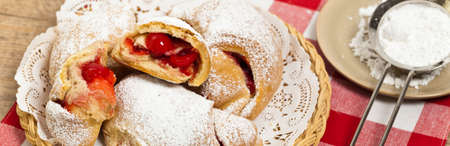 powdered: Breakfast Pastries with cherry jam and powdered sugar. Selective focus.