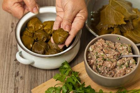 greek cuisine: Old woman making Stuffed Grape Leaves. Dolma. Azerbaijan, Turkish and Greek Cuisine. Selective focus.