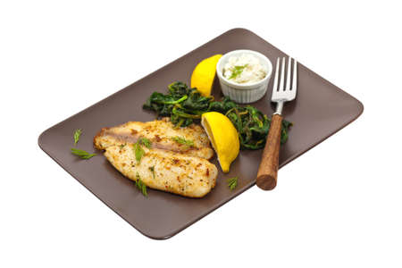 whitefish: Baked Fish Fillet with Sauteed Spinach on white background. Selective focus. Stock Photo