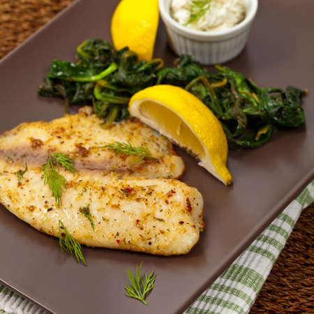 Tilapia with Sauteed Spinach. Selective focus.