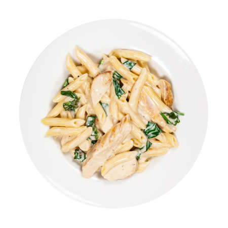 Chicken Alfredo Pasta with Spinach Isolated on White. Selective focus. Stock Photo