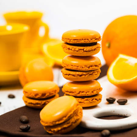 Orange French Macarons with Dark Chocolate and Coffee Filling. Selective focus. Stock Photo