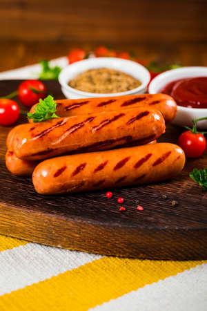 Grilled Sausages on Fork on Wooden Background. Selective focus.