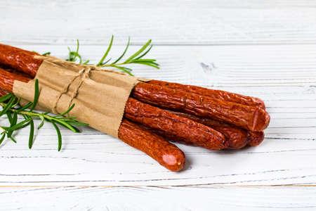 Kabanos or Cabanossi Thin Dry Smoked Polish Sausage on White Wooden Background. Selective focus. Zdjęcie Seryjne