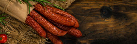 Kabanos or Cabanossi Thin Dry Smoked Polish Sausage on Wooden Background. Selective focus. Zdjęcie Seryjne