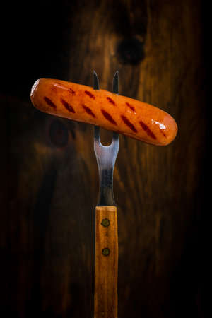 Grilled Sausages on Fork on Wooden Background. Selective focus.