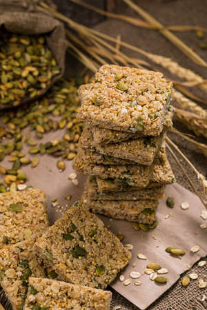 Multigrain Cereal Crunchy Squares Bars with Pumpkin Seeds Background. Healthy Bar Snack. Selective focus.