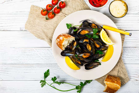 Delicious Seafood Mussels with Lemon and Parsley. Clams in the Shells on Wooden Background. Selective focus.