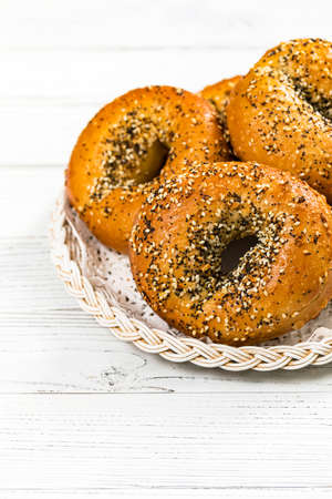 Freshly Baked Bagels Topped with Sesame Seeds, Poppyseeds, Garlic and Onion on Wooden Background. Selective focus.