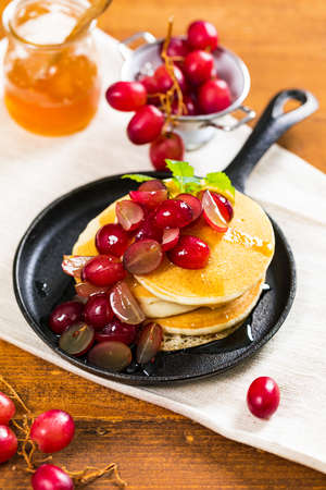 Stack of Pancakes with Sliced Red Grapes and Maple Syrup. Selective focus.