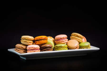 Colorful Macaroons Chocolate, Pistachio, Cherry, Orange, Vanilla Flavor Background on Black Background. Selective focus.