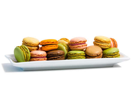 Colorful Macaroons Chocolate, Pistachio, Cherry, Orange, Vanilla Flavor Background Isolated on White Background. Selective focus.