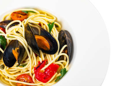 Delicious Seafood Pasta Spaghetti with Mussels and Tomatoes Isolated on White Background. Italian Cuisine. Selective focus.