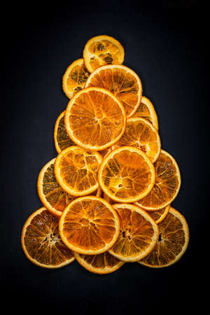 Christmas Tree Made with Dry Oranges Slices Snack on Black Background for Christmas Decorations. Selective focus.