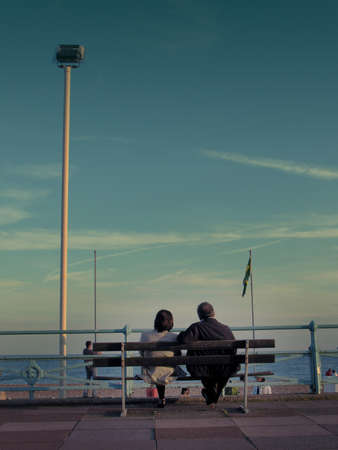 A senoir married couple sitting on a bench against beach and sea, enjoying their golden years. Brighton. Stock Photo - 11580430