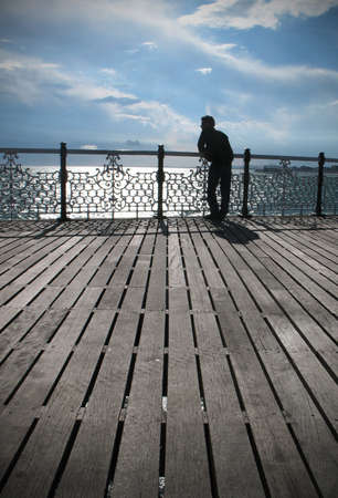 A young man looking into the distance, coast, Brighton, Pier