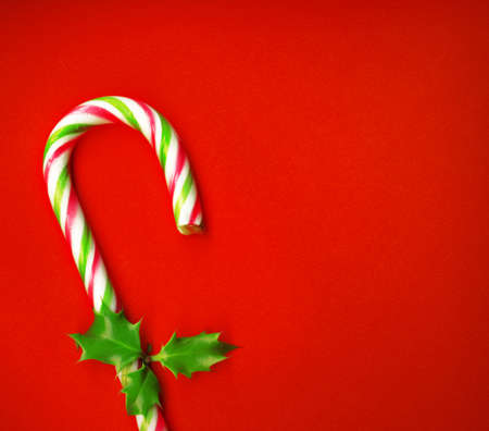 carol: Candy cane with pretty holly leaves on red background, candy cane Stock Photo