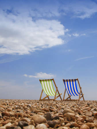 deck chairs: Subject: view of two traditional deck beach chairs , alone on a quiet, clean, sunny beach.  Location: Brighton UK.