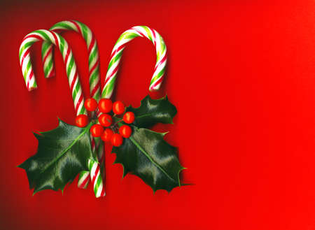 carol:  Candy cane with pretty holly leaves and berries on red background, candy cane
