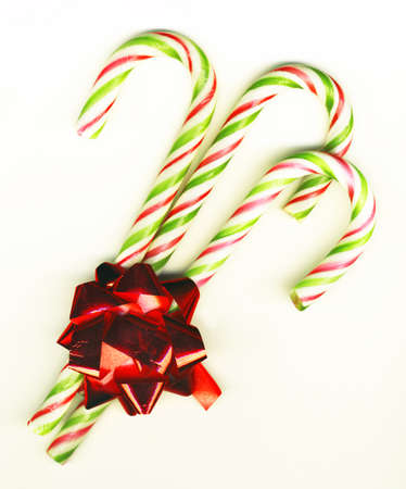 Three candy canes with red bow on white background isolated, Christmas background photo
