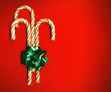 minty: Candy cane with green bow on red background, candy cane