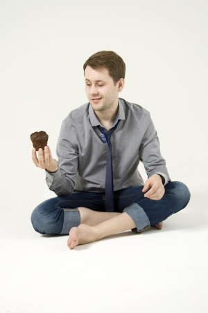blow out: Man celebrating his birthday; holding a cupcake