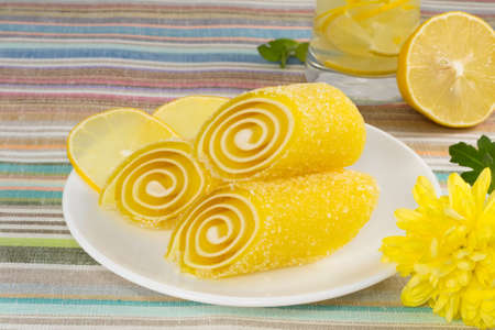 yellow candy fruit on a plate with lemon and flower photo