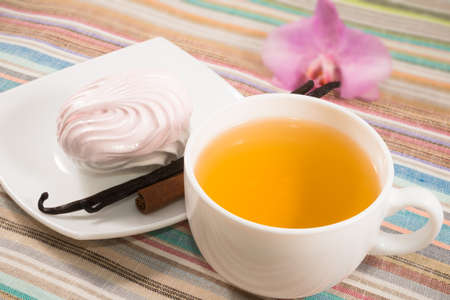 cup of tea and pink marshmallow on a saucer with a vanilla, cinnamon photo