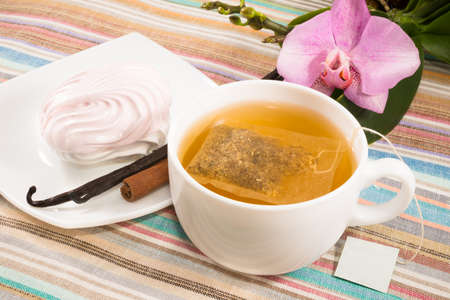 cup of tea with tea bag and pink marshmallow on a saucer with a vanilla, cinnamon photo