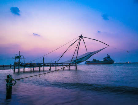 Kochi chinese fishnets and vessel on sunset  in Kerala. Fort Kochin,  South India photo