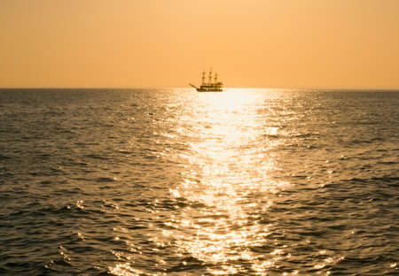 silhouette ancient a vessel floating by sea at sunset photo