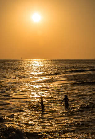 silhouettes of two girls at sunset, swimming in the sea Stock Photo