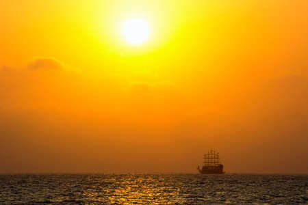 Sea with silhouette of the ancient ship at sunset photo