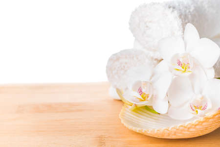 Spa still life with white orchid, shell and towel on wood background photo
