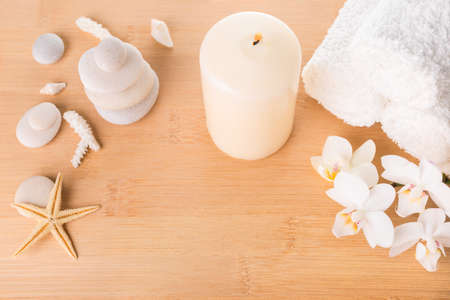Spa still life with orchid, stones, candle burning and towel on wood background photo