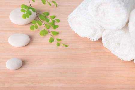 Spa still life with stone, green  branch  and white towel on wood background photo