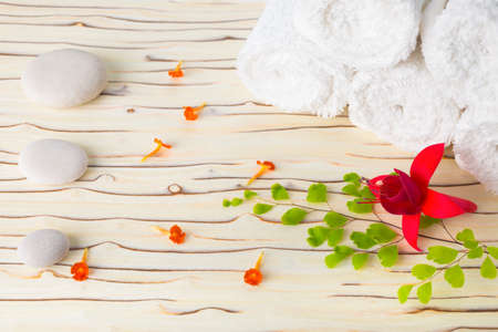 Spa still life with stone, flowers  and white towel on wood background photo
