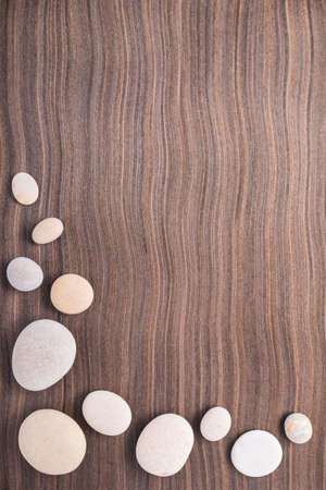 light pebbles on wooden ebony tree background photo