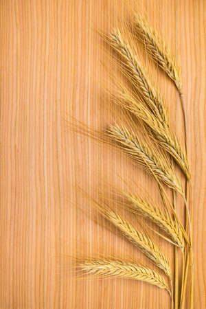 ripe golden ears of wheat on the wooden background photo