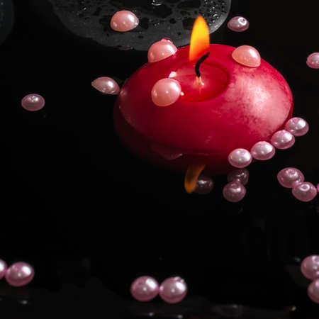 perle rose: Beau cadre thermale de d�licates perles de nacre rose et bougie sur l'eau, gros plan Banque d'images
