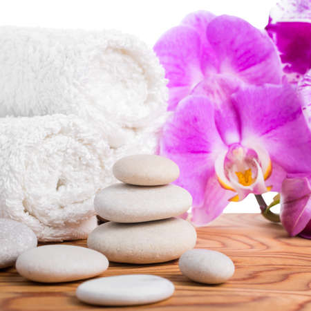 Spa setting with stones, lilac orchids and towels is isolated on white background