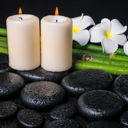 spa concept of zen basalt stones, two white flower frangipani, candles and natural bamboo with drops, closeup  photo