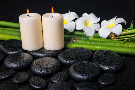 spa concept of zen basalt stones, three white flower frangipani, candles and natural bamboo with drops, closeup  photo