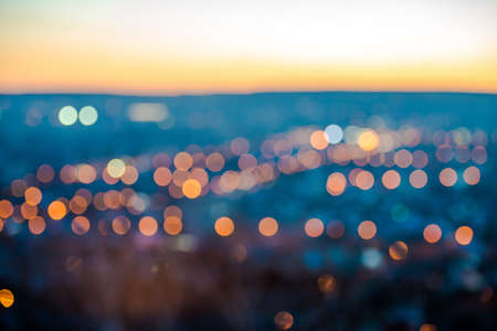 outdoor electricity: city blurring lights abstract circular bokeh on blue background with horizon, closeup   Stock Photo