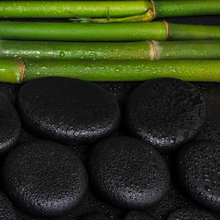 spa setting of zen basalt stones and natural bamboo with drops, closeup photo