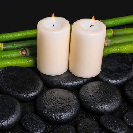 spa concept of zen basalt stones,  candles and natural bamboo with dew, closeup  photo