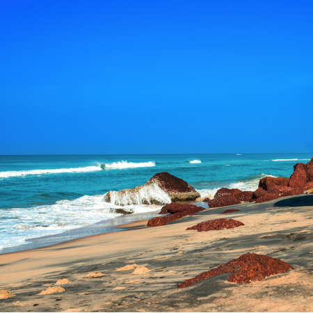 Beautiful tropical coast with big stones and black sand of the Indian Ocean. Varkala, Kerala. India photo