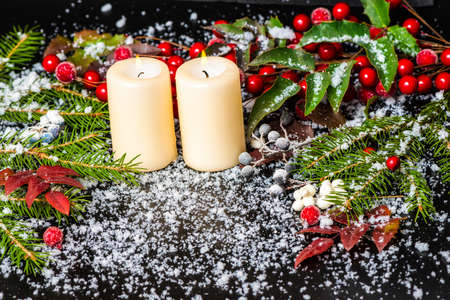 Greeting Christmas card of evergreen branches, red leaves, berry with snow and candles, closeup photo